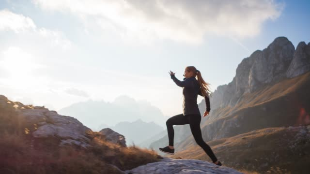 vídeos de stock e filmes b-roll de sport active woman running uphill over rocky trails and grassy slopes in mountain terrain - correr