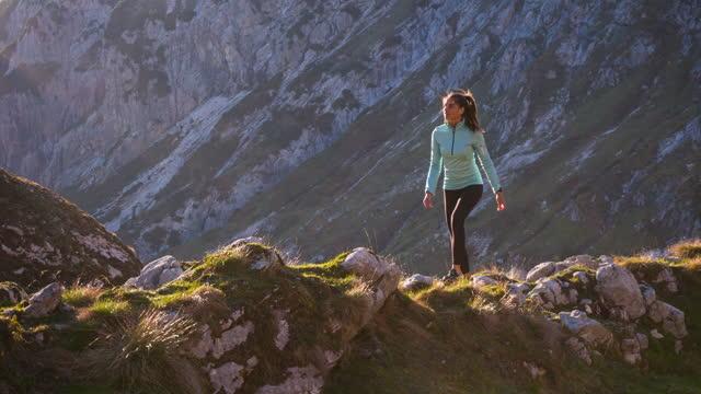 vídeos y material grabado en eventos de stock de mujer activa deportiva dando un paseo cuesta arriba sobre senderos rocosos y pistas de hierba en terreno de montaña - pico montaña
