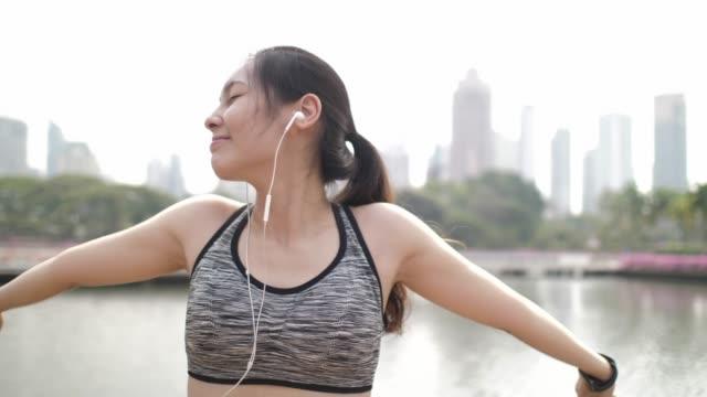 stockvideo's en b-roll-footage met sport aziatische vrouw versheid en arm getogen op ochtend - gymbroek