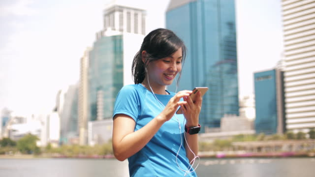 sport asian woman using smart phone - in ear headphones stock videos & royalty-free footage
