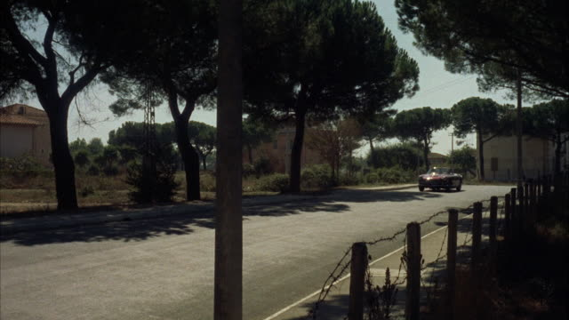 ms pan sport car in motion / rome, italy - anno 1960 video stock e b–roll