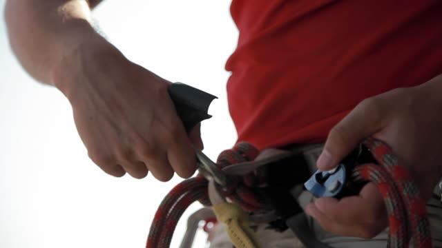 C/U sport climber preparing the rope in the harness