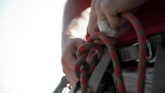 c/u sport climber preparing the rope in the harness - sicurezza video stock e b–roll