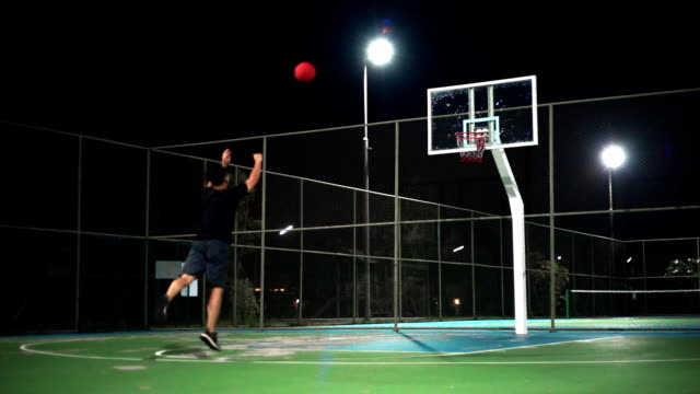 Sport Concepts: A man playing basketball on outdoor court by himself at night.