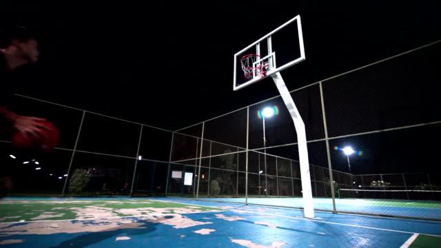 vídeos de stock e filmes b-roll de slo mo sport concepts: a man playing basketball on outdoor court by himself at night. - fintar desporto