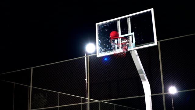 vídeos de stock e filmes b-roll de slo mo sport concepts: basketball going through the hoop on outdoor court at night. - fintar desporto