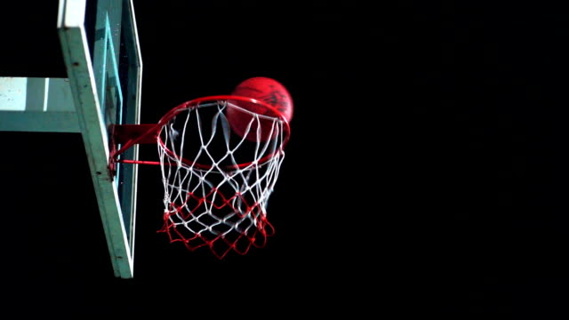 Sport Concepts: Basketball going through the hoop on outdoor court at night.