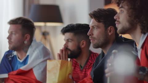 sport fans sitting on couch watching tv and cheering - åskådare människoroller bildbanksvideor och videomaterial från bakom kulisserna