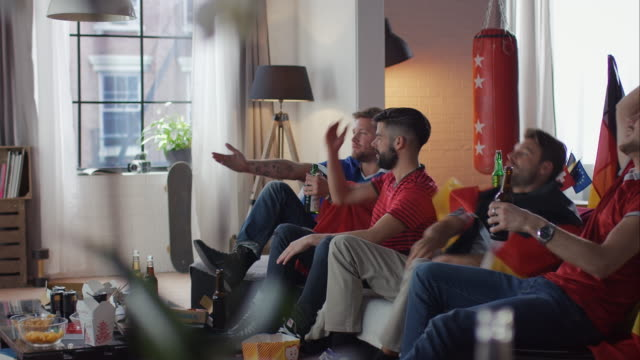 Sport fans sitting on couch watching tv disappointed