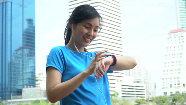 sport girl looking at smartwatch in city view - bracelet stock videos & royalty-free footage