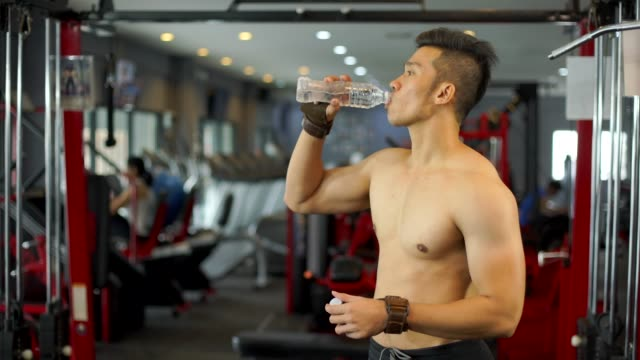 Sport Man Drink Water In Gym