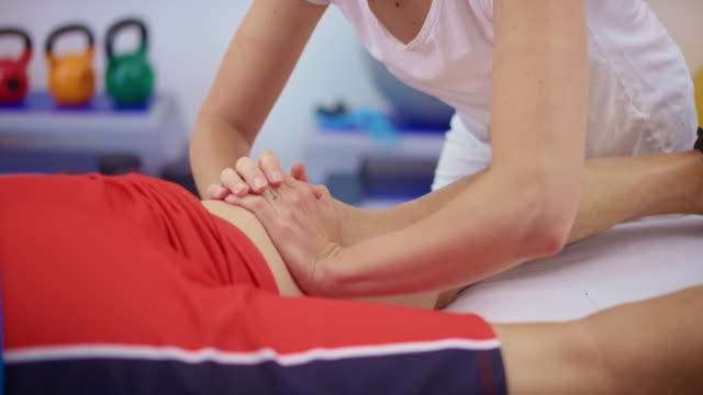 stockvideo's en b-roll-footage met slo mo sport massage therapeut masseren van een cliënt dij - massagetafel