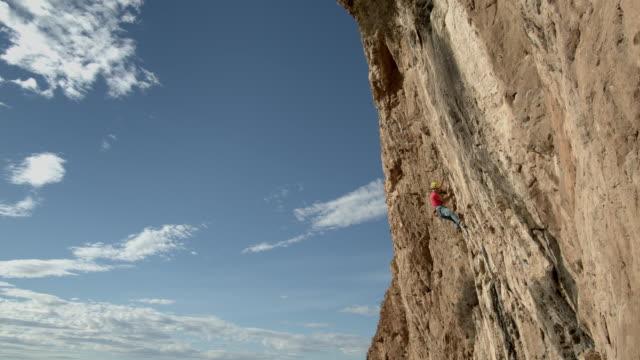 vídeos de stock, filmes e b-roll de sport rock climber as he ascends sandstone rock face. - corda de escalada