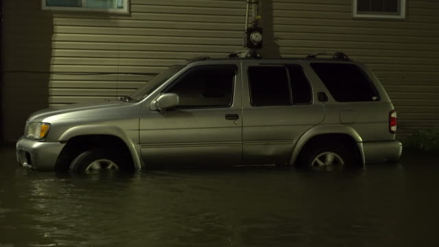 A sport utility vehicle parked near the water becomes partially submerged in tidal surge as Jamaica Bay overflows it's banks during the night time...