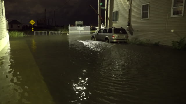 A sport utility vehicle parked on a residential street at night in Queens New York is partially submerged in tidal flooding as Jamaica Bay overflows...