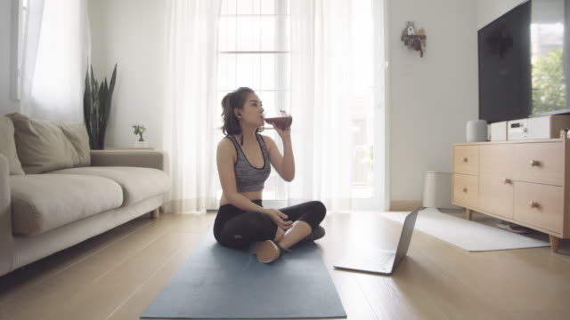 sport woman drinking a protein shake at a home. - smoothie stock videos & royalty-free footage
