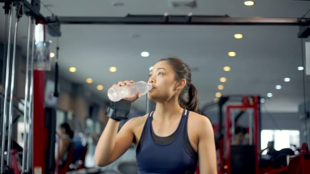sport woman drinking water in gym - lap body area stock videos & royalty-free footage