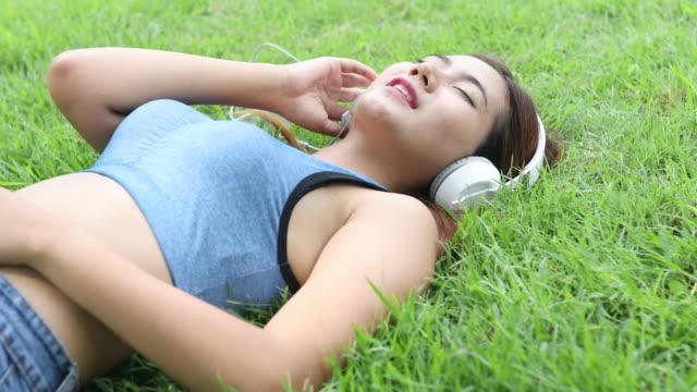 Sport vrouw genieten van de muziek op gras