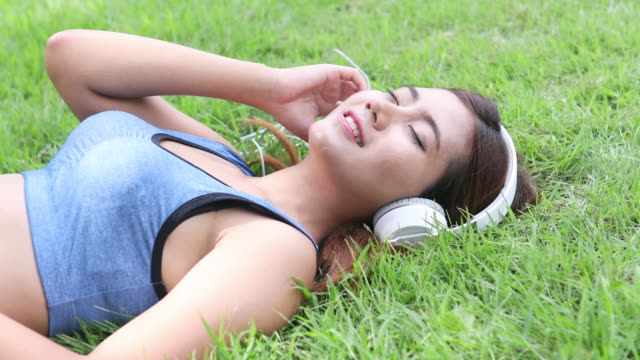 sport woman enjoying the music on grass - one teenage girl only stock videos & royalty-free footage