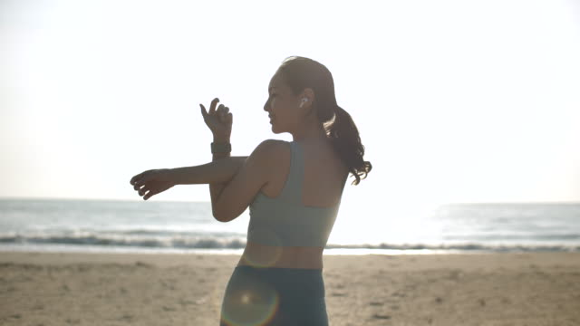 sport woman stretch at beach on morning, preparing for workout - human muscle stock videos & royalty-free footage