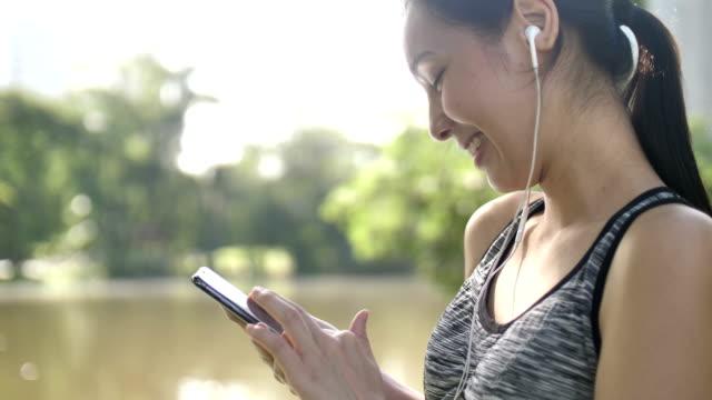 sportlerin mit telefon während des trainings im park - software stock-videos und b-roll-filmmaterial