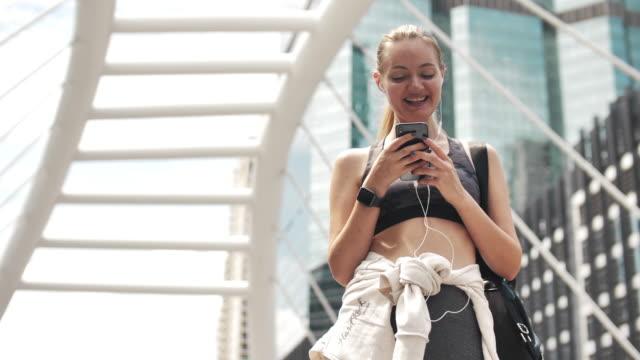 sport woman using smart phone in city - sportswear stock videos & royalty-free footage