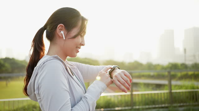 sport woman using smart watch in city at morning - interval start stock videos & royalty-free footage