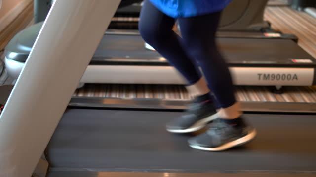 vidéos et rushes de femmes de sport exécutant sur l'équipement cardio de tapis roulant - joggeuse