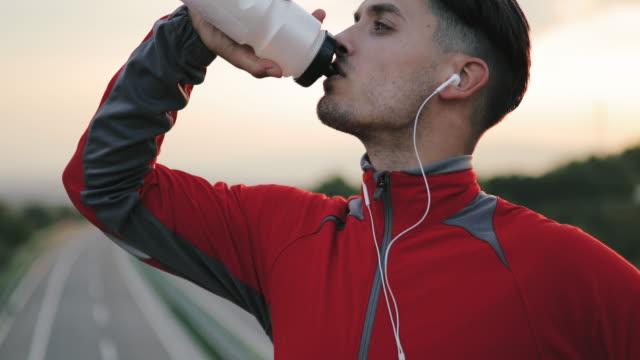 sport. junge sportlerin trinkwasser aus der flasche nach - trinken stock-videos und b-roll-filmmaterial