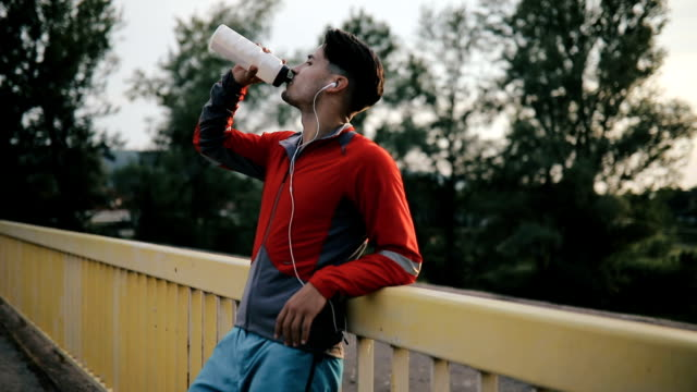 Sport. Young athlete drinking water of bottle after running