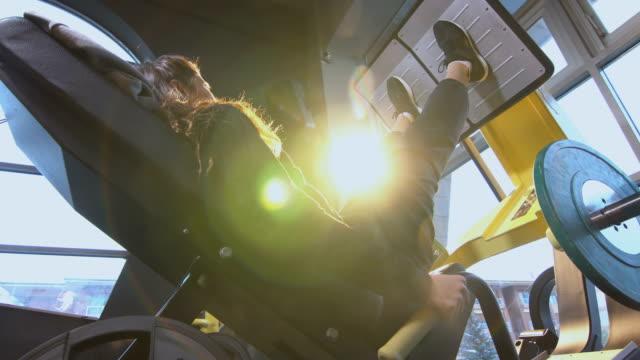 sportive female doing leg press exercise in gym - leg press stock videos & royalty-free footage