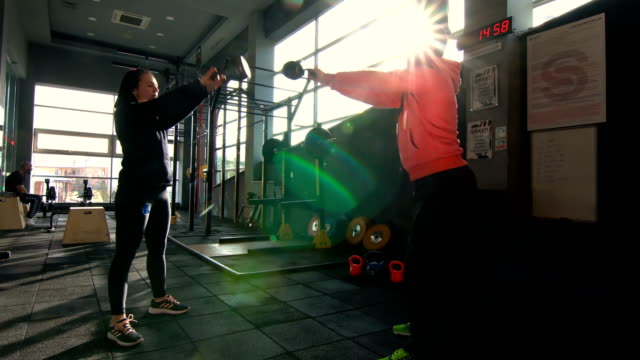 sportive male and female doing kettlebell squat in gym - crouching stock videos & royalty-free footage