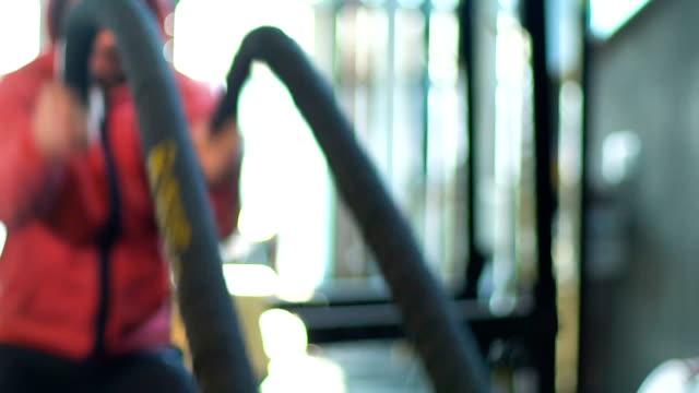 vídeos y material grabado en eventos de stock de hombre deportivo haciendo ejercicio cuerda de batalla en gym - remo con espadilla