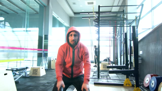 Sportive Man Doing Battle Rope Exercise in Gym