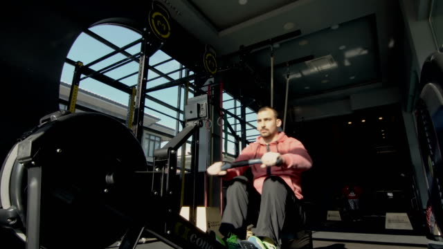 sportive man doing row exercise in gym - rowing machine stock videos & royalty-free footage