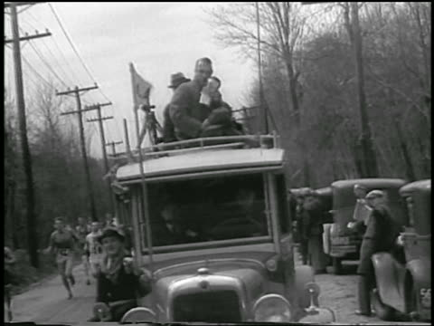 b/w 1933 sports announcer with microphone riding atop truck in boston marathon - 1933 stock videos and b-roll footage