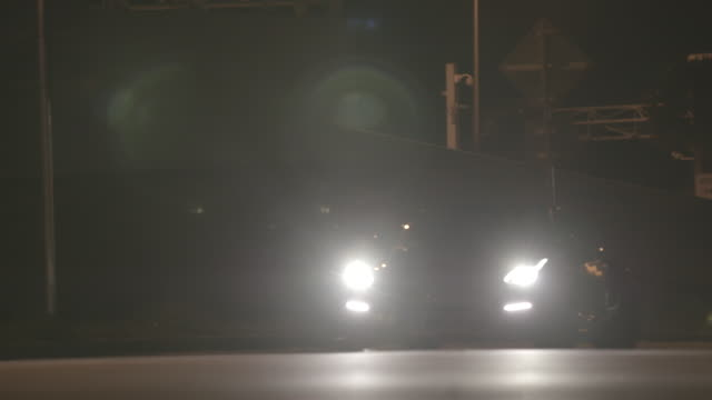 sports car drives up road at night - fanale anteriore video stock e b–roll