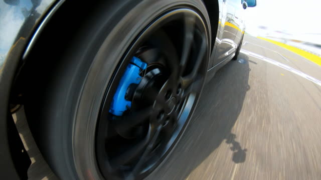 sports car driving at a motor racing track in pursuit of competition, crossing starting / finish line - pursuit sports competition format stock videos & royalty-free footage
