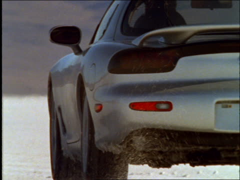 Sports car driving away from camera in desert