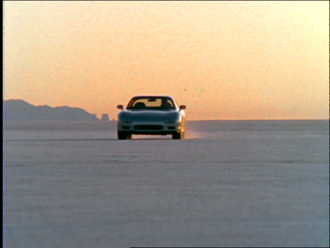 Sports car driving toward camera in desert at twilight
