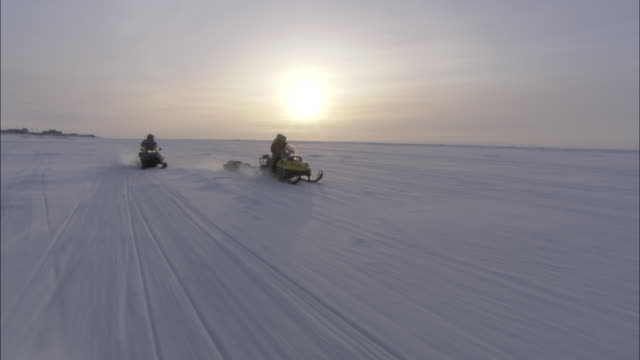 sports enthusiasts on snowmobiles follow tracks as they drive across a snowy wilderness. - sledge stock videos & royalty-free footage