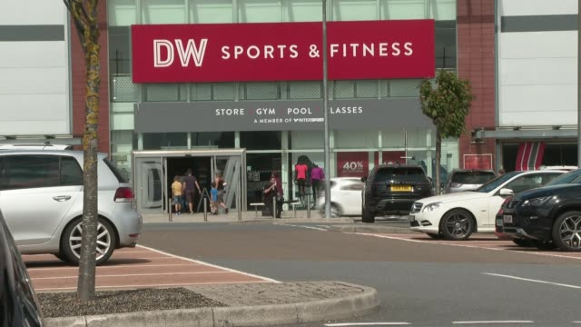 sports falls into administration; scotland: ext gv dw sports and fitness store shoppers past store wearing face masks sign 'dw sports & fitness' gv... - itvイブニングニュース点の映像素材/bロール