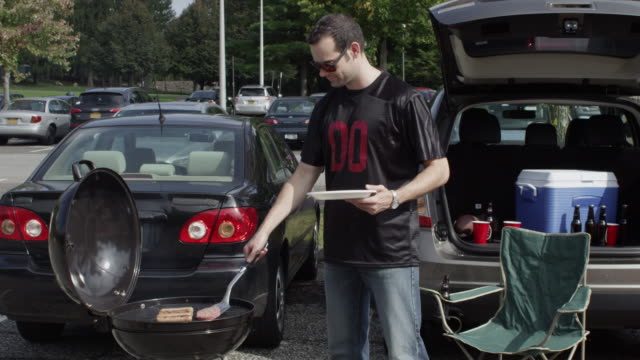 Sports fan retrieving food from the grill at a tailgating party