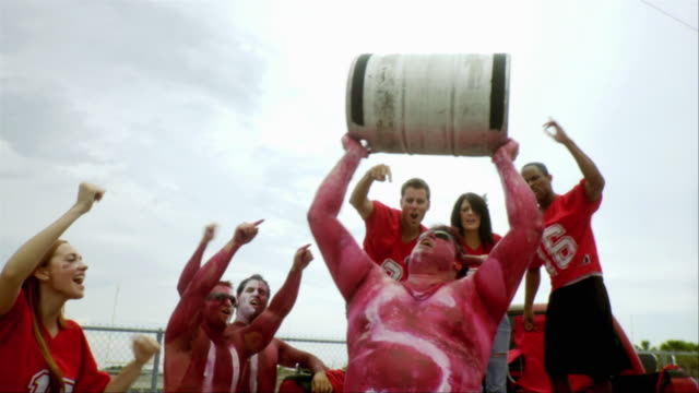 slo mo ms sports fan wearing body paint holding keg of beer in air, others cheering, jacksonville, florida, usa - keg stock videos and b-roll footage