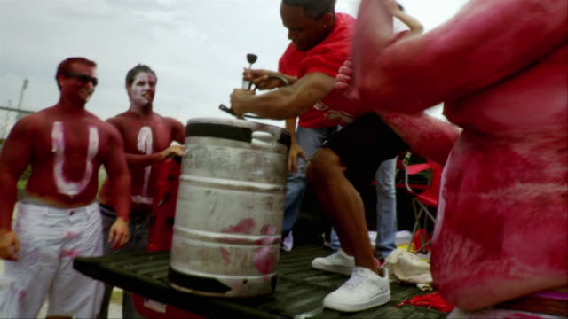 slo mo ms sports fans celebrating with keg of beer on truck, jacksonville, florida, usa - keg stock videos and b-roll footage