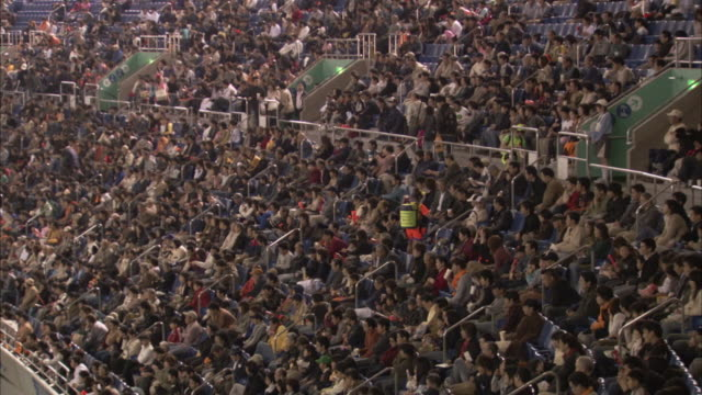sports fans in a stadium cheer and hit sticks together. - スタンド席点の映像素材/bロール