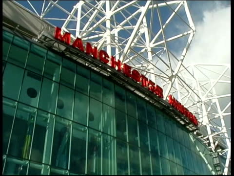 football companies guilty of price fixing; itn file from server england: manchester: old trafford: ext manchester united megastore tilt up to... - megastore stock videos & royalty-free footage