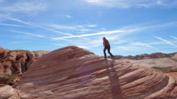 Sports Hiking Woman Climbs Up The Red Rock Background The Sky Slow Motion 4K