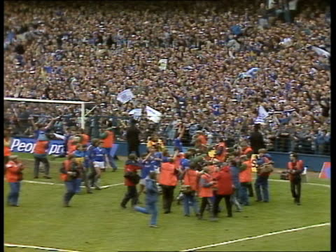 stockvideo's en b-roll-footage met report on football and tv rights everton lts everton players on pitch surrounded goodison pk by press after beating qpr for the stock canon league... - 1985