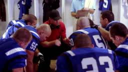 Sports team huddles in locker room